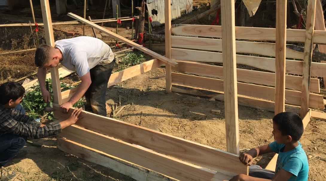 Volunteers help build a chicken coop at a school in Nepal.